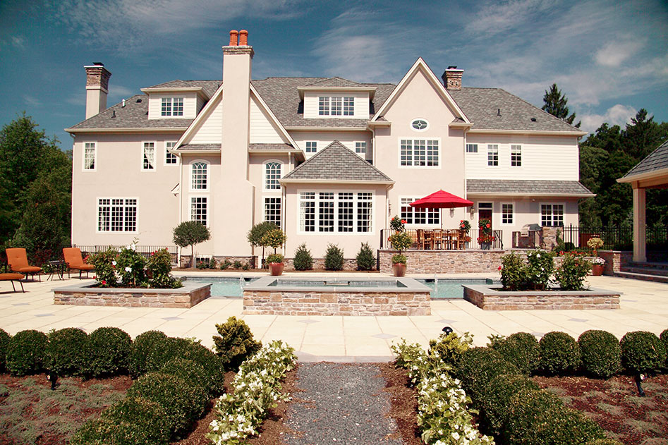 back of large white mansion with pool